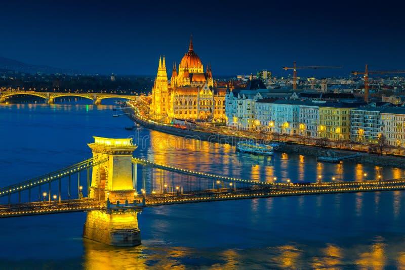 Iluminated kedjebro och parlamentbyggnad på skymning, Budapest, Ungern royaltyfria bilder