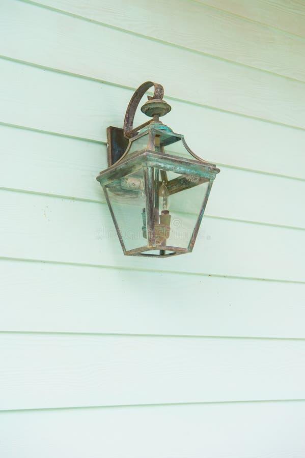 Iluminazione pubblica Retro lampione d'annata sulla parete di legno del turchese La vecchia lanterna di rame con patina sembra an fotografia stock