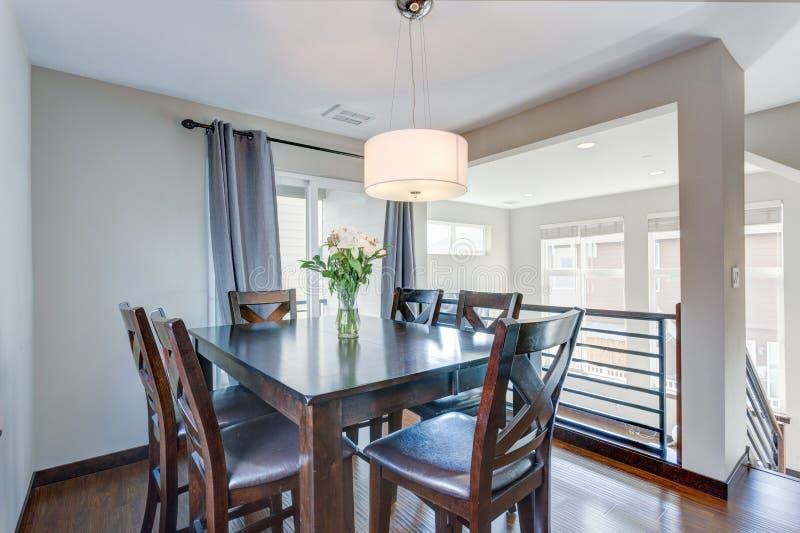 Ilumine a sala de jantar enchida com grupo de madeira escuro da tabela fotos de stock royalty free