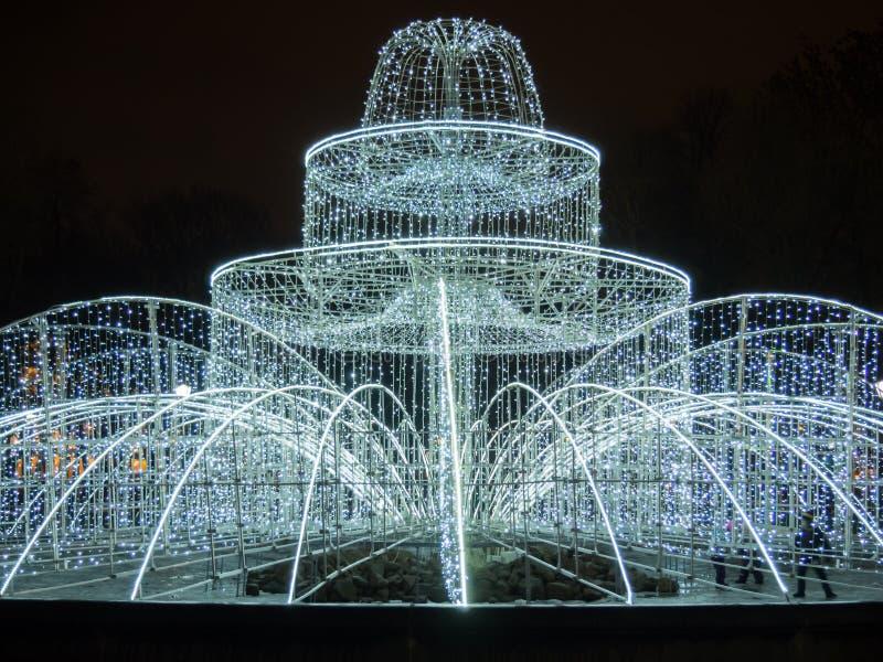 Iluminująca fontanna dekorował z girlandami i bożonarodzeniowe światła, dekoracja elementy przy nocą petersburg Rosji st obrazy stock