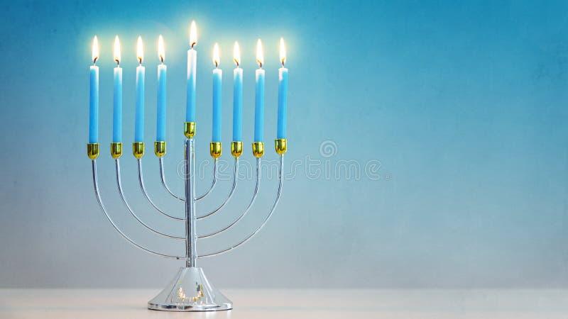 Iluminujący Hanukkah Menorah błękita tło zdjęcie royalty free