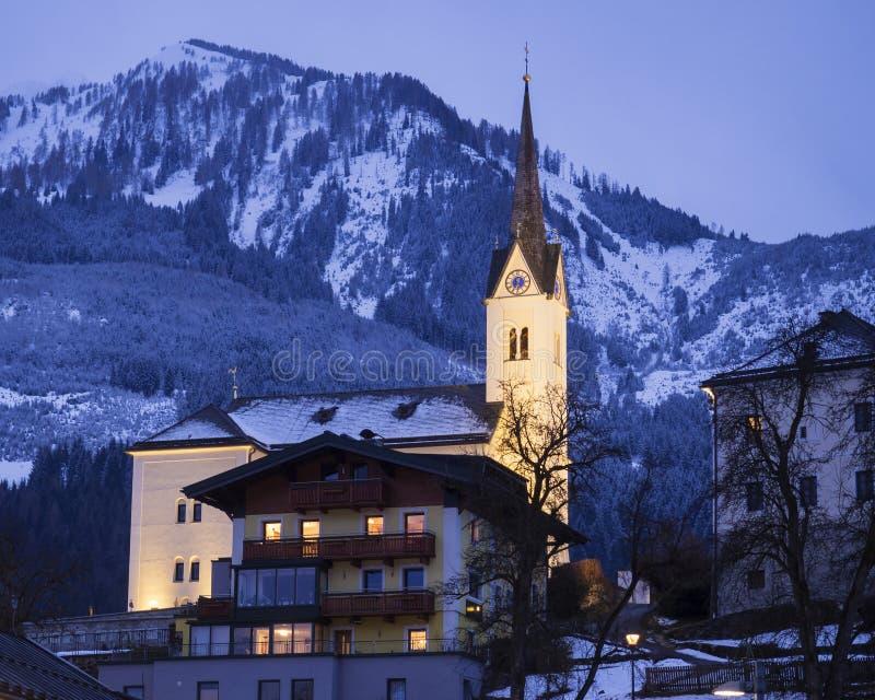 Iluminujący kościół katolickiego St Margaretha z ulicą, światłami, górami i lasem w Kaprun Austria przy błękitną godziną, zdjęcie stock