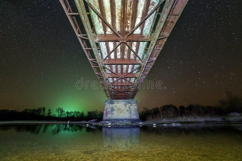 Iluminujący metalu most na betonów poparciach odbijał w wodzie na ciemnym gwiaździstym nieba tle, dolny widok kolory wykładają no fotografia stock