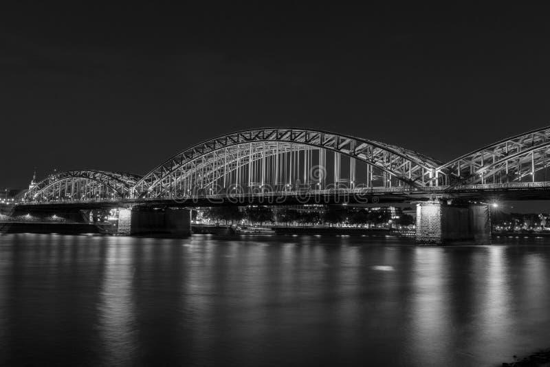 Iluminujący most w Kolonia przy nocą w czarny i biały obrazy royalty free