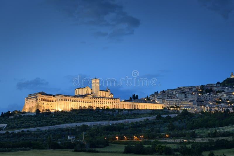 Iluminujący pejzażu miejskiego Assisi monaster i bazylika obraz stock