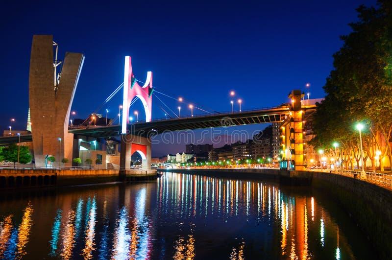 Iluminujący Salbeko zubia most nad Nevion rzeką w Bilbao, Hiszpania przy nocą obraz royalty free
