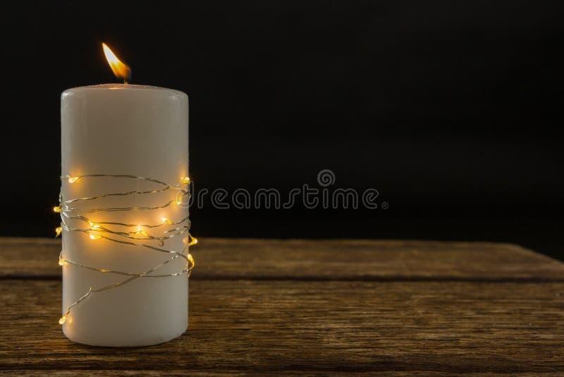 Iluminujący sznurków światła zawijający na zaświecającej świeczce obraz stock