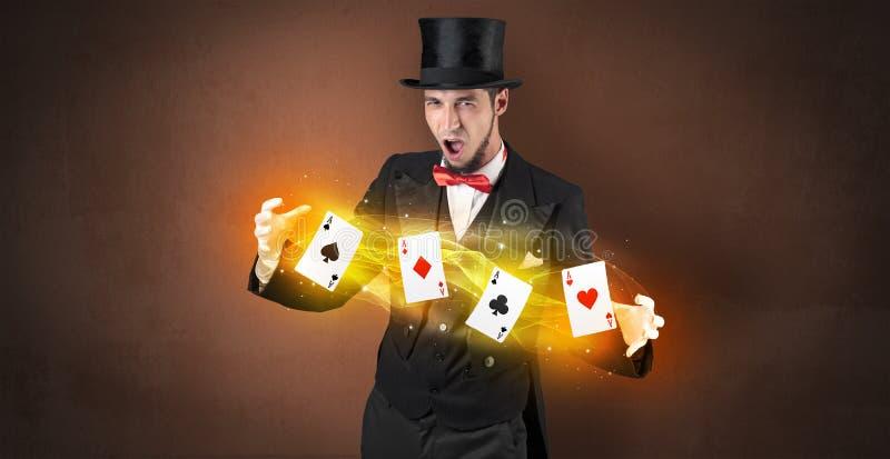 Ilusionista que faz o truque com os cartões mágicos do jogo fotografia de stock