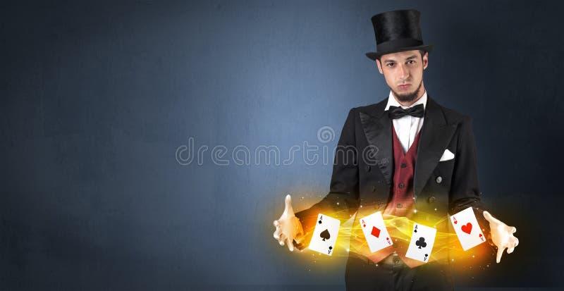 Ilusionista que faz o truque com os cartões mágicos do jogo fotos de stock