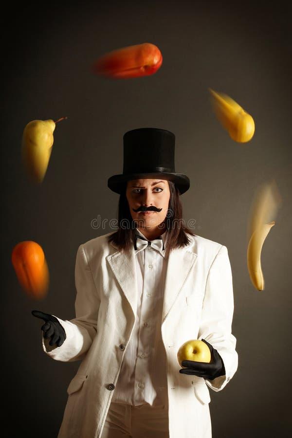 Ilusionista que hace juegos malabares con las frutas fotos de archivo