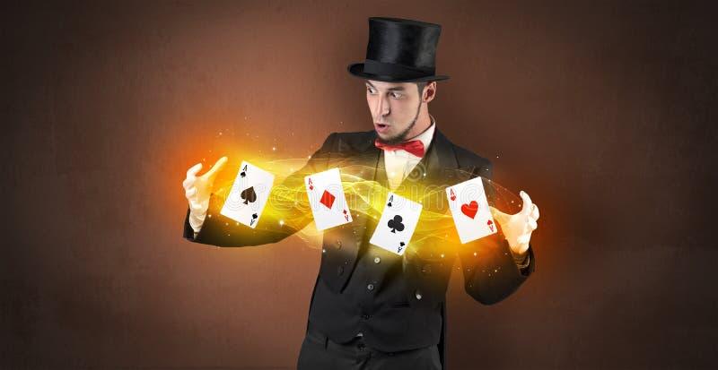 Ilusionista que hace truco con las tarjetas mágicas del juego fotos de archivo libres de regalías
