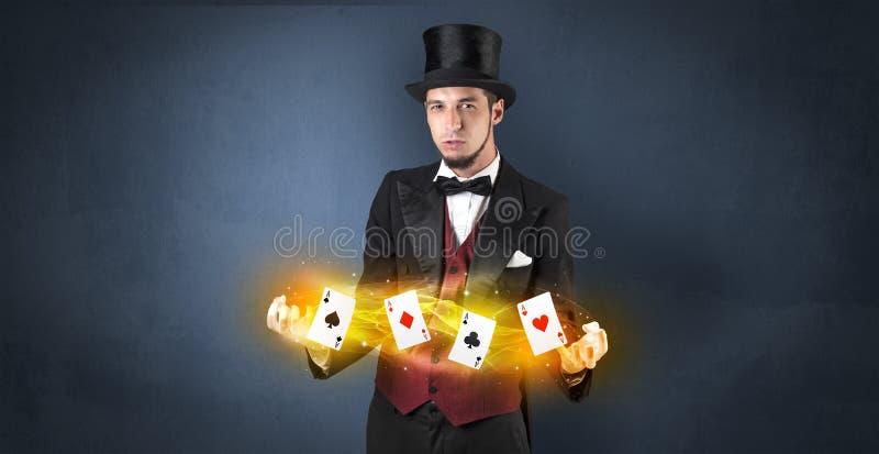 Ilusionista que hace truco con las tarjetas mágicas del juego fotografía de archivo libre de regalías