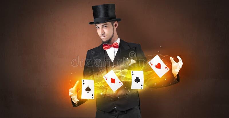 Ilusionista que hace truco con las tarjetas mágicas del juego foto de archivo