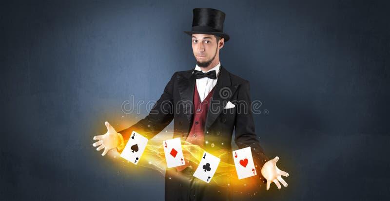 Ilusionista que hace truco con las tarjetas mágicas del juego fotografía de archivo