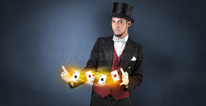 Ilusionista que hace truco con las tarjetas mágicas del juego imagenes de archivo