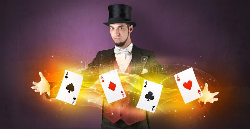 Ilusionista que hace truco con las tarjetas mágicas del juego imagen de archivo libre de regalías