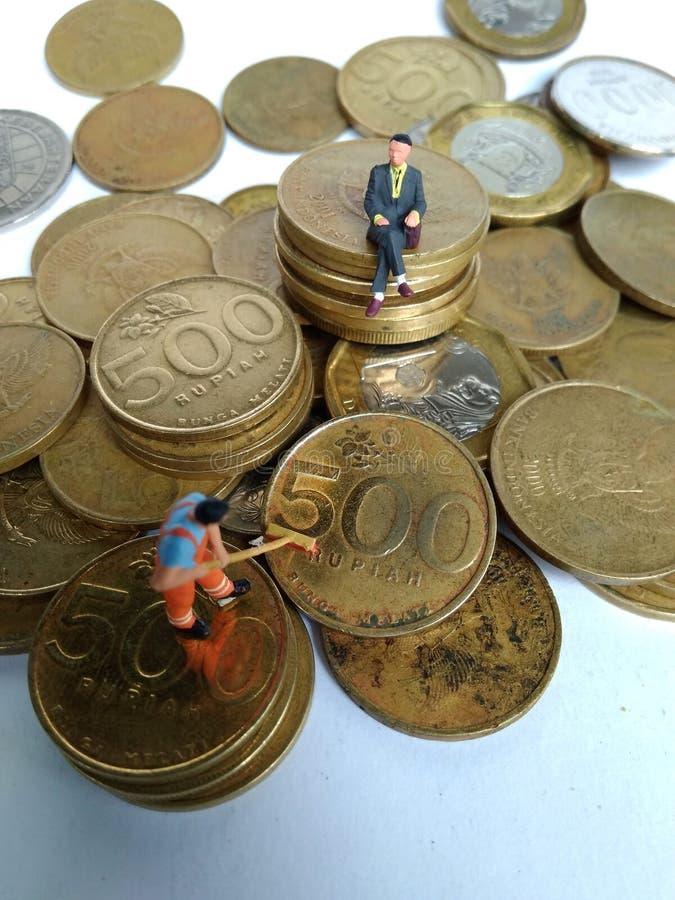 Ilustração conceptual para a atividade da lavanderia do dinheiro, mini figura brinquedo do trabalhador que limpa a moeda dourada  imagens de stock royalty free