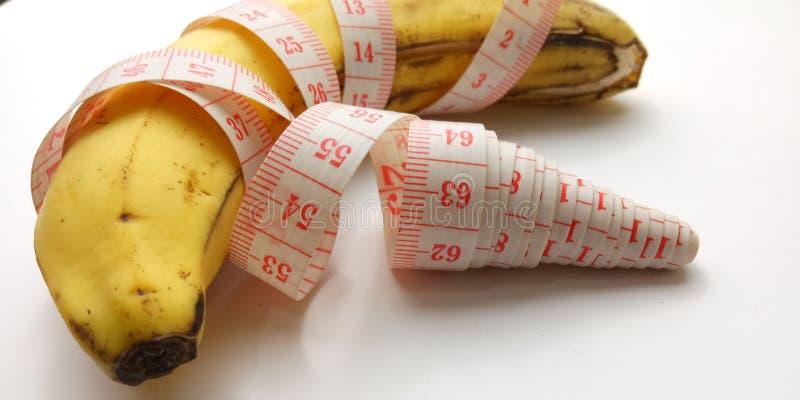 Ilustração conceptual para o tamanho do pênis, banana com medidor plástico cor-de-rosa do alfaiate no fundo branco fotos de stock royalty free
