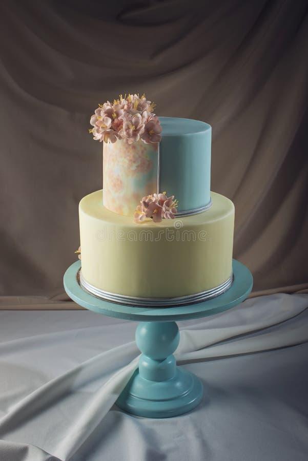 ilustraciones Pastel de bodas adornado en estilo en colores pastel con las flores rosadas fotos de archivo