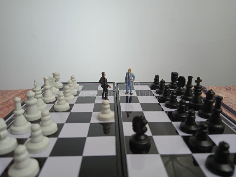 Ilustracja na fotografię Koncepcja wojny, bitwy lub sytuacji politycznej, 2 stojąca mini figura, negocjacje lub debata poza szach obrazy royalty free
