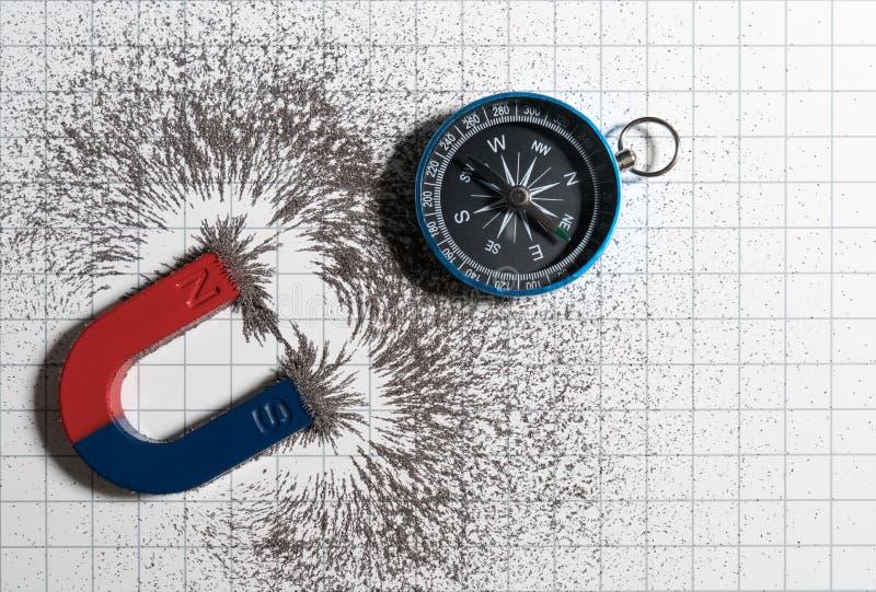 Imán de herradura rojo y azul o la física magnética y compás con el campo magnético del polvo del hierro en fondo del gráfico del fotografía de archivo libre de regalías