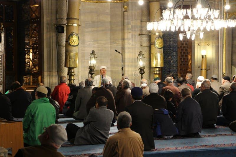 Imã, lendo o Alcorão na mesquita nova Istambul fotografia de stock royalty free