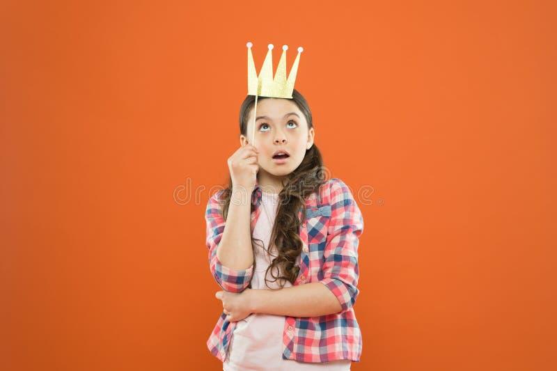 Im这里一个高级领导 一点在橙色背景的高级领导 逗人喜爱的女孩上司佩带的支柱冠 有大的小愉快的孩子 库存图片