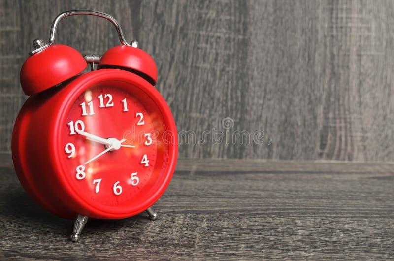 Im altem Stil rote Uhr auf einem hölzernen Hintergrund lizenzfreie stockbilder