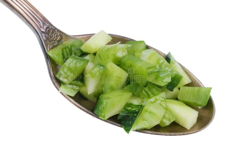 Im alten goldenen Löffel gibt es Stückchen Nahrung - grünes gehacktes lokalisiertes Makro des Markkürbisses Zucchini stockbild