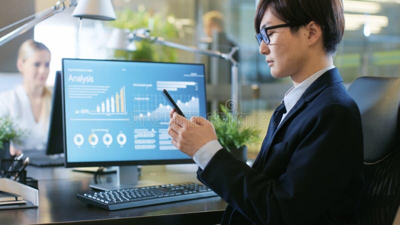 Im Büro-asiatischen Geschäftsmann Uses Smartphone, Schreibenimportan lizenzfreie stockfotos