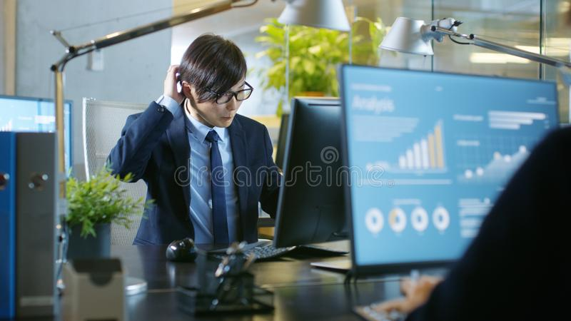 Im Büro aufgeregte arbeitet der Geschäftsmann an einem persönlichen Tischplattenc lizenzfreie stockfotos