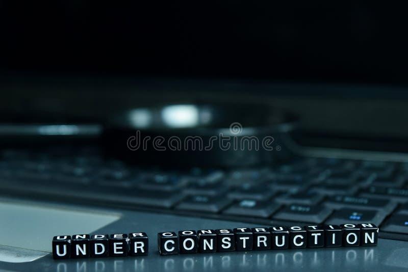 Im Bau Textholzklötze im Laptophintergrund Geschäfts- und Technologiekonzept stockbild