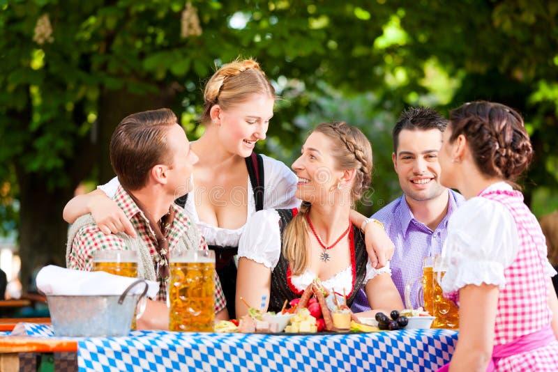 Im Biergarten - Freunde auf einer Tabelle mit Bier lizenzfreies stockbild