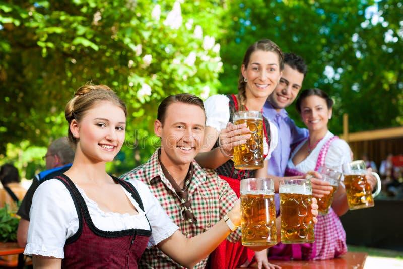 Im Biergarten - Freunde, die Bier trinken stockfotografie