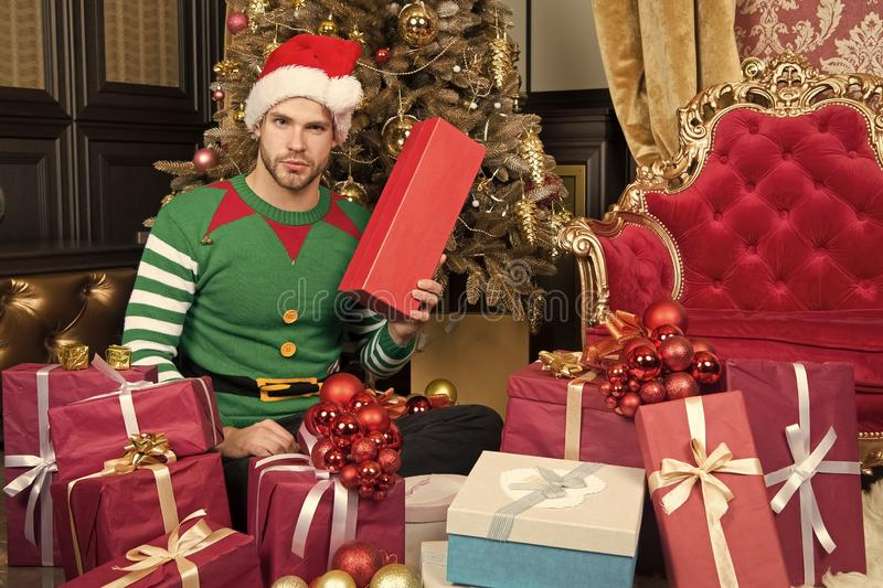 Im a big fan of Christmas. Guy is celebrating Christmas at home. Man in santa hat hold Christmas presents. Happy man stock image