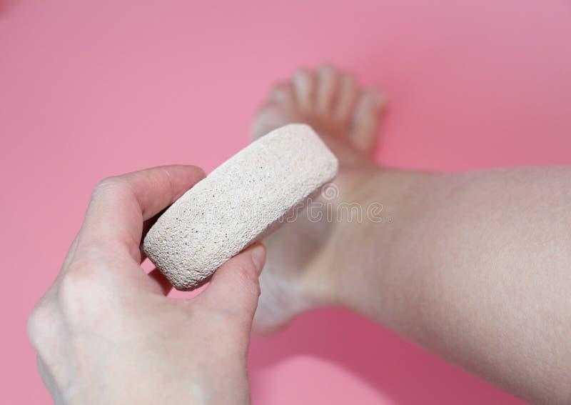 Im Foto hält eine Frauenhand einen Bimsstein nahe der Ferse ihres Fußes stockbild