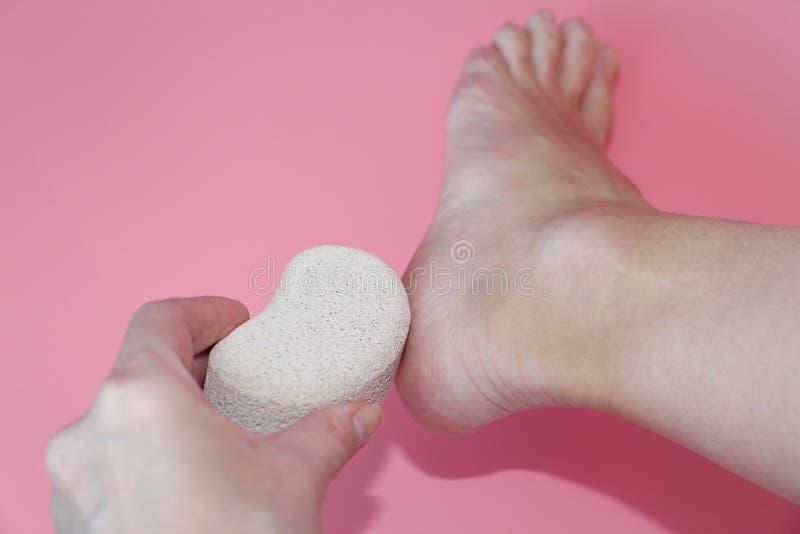 Im Foto hält eine Frauenhand einen Bimsstein nahe der Ferse ihres Fußes stockbilder