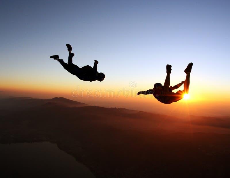 Im freien Fall springen des Sonnenuntergangs über dem Meer und den Bergen lizenzfreie stockfotografie