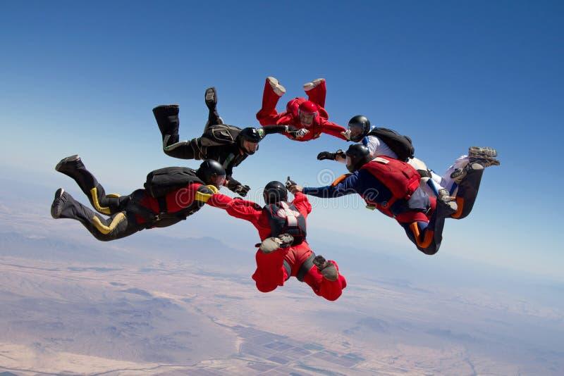 Im freien Fall springen von Leuteteamwork stockfotografie