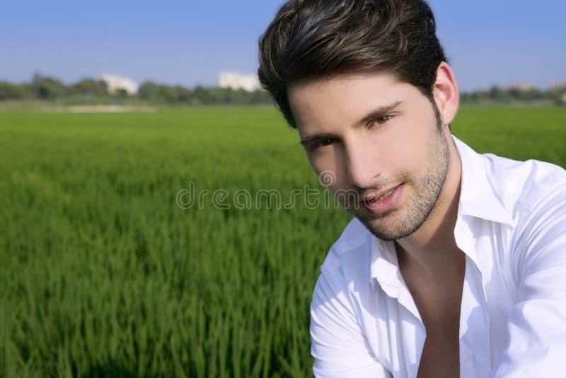 Im Freienglückliches des jungen Mannes in der grünen Wiese lizenzfreie stockbilder