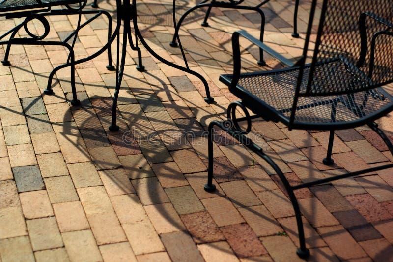 Im Freienmöbel auf einem Ziegelsteinpatio stockbilder