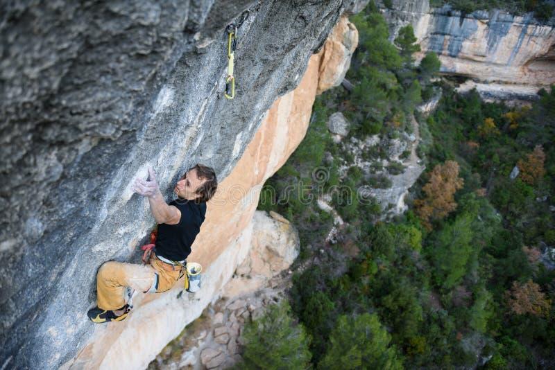 Im Freiensport Aufsteigender Kletterer eine schwierige Klippe Extremes Sportklettern stockfotos