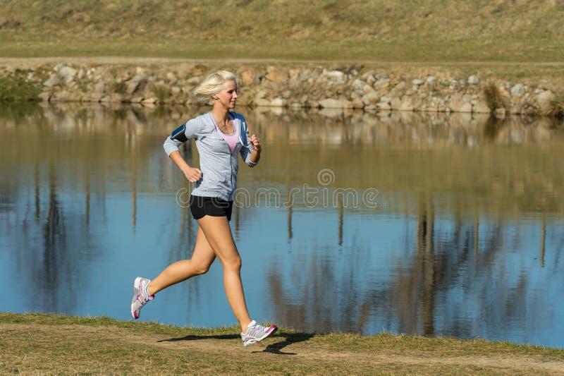 Im Freiensport der laufenden Frau durch Flussquerneigung stockbilder