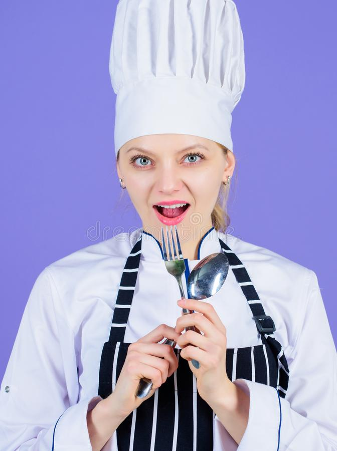 Im a great cook. Sensual lady cook. Pretty cook holding stainless steel spoon and fork. Professional woman cook wearing. Traditional white chef hat and apron royalty free stock image