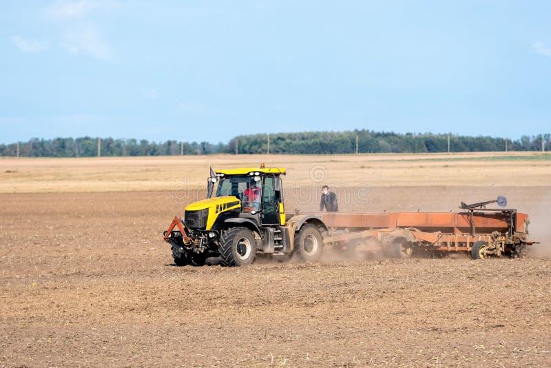 Im Herbst verarbeitet der Landwirt die Felder mit dem Traktor und sät die Samen für die folgende Ernte lizenzfreie stockfotos