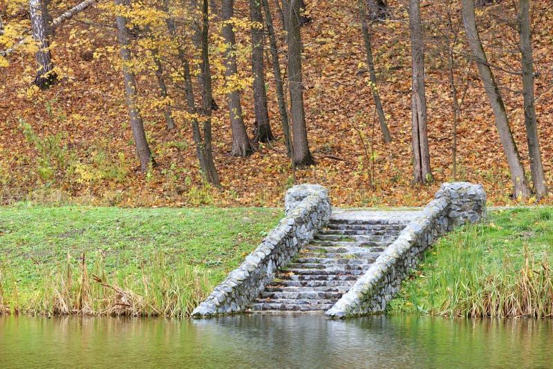 Im Herbstteich hinunter die alten Steinschritte lizenzfreie stockfotos