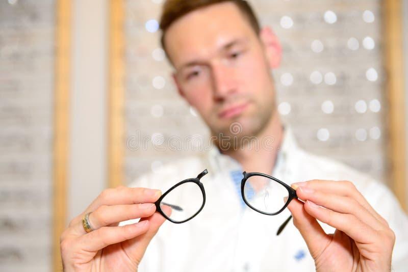 Im jungen Mann des Optikergeschäftes mit defekten Gläsern lizenzfreie stockfotografie