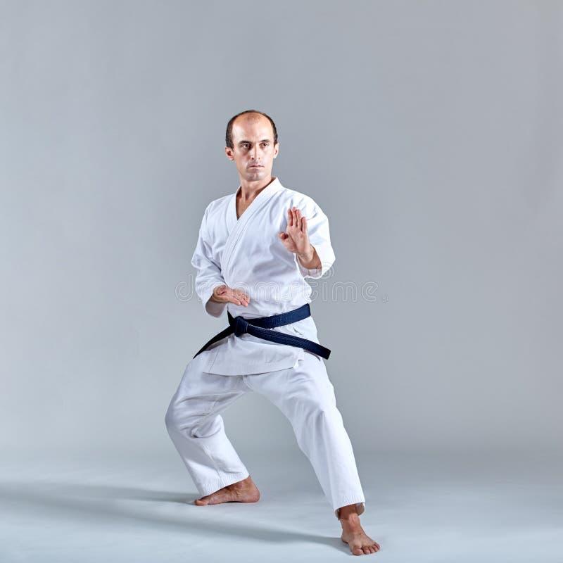 Im Karategestell bildet ein erwachsener Athlet eine formale Karateübung aus stockbilder