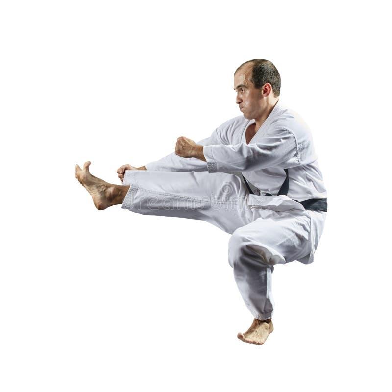 Im karategi bildet ein erwachsener Sportler einen Tritt in einem Sprung gegen einen weißen lokalisierten Hintergrund aus stockbilder