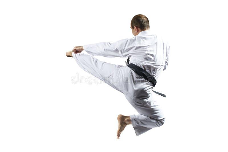 Im karategi schlägt ein Athlet einen Tritt im Sprung gegen einen weißen lokalisierten Hintergrund lizenzfreies stockfoto